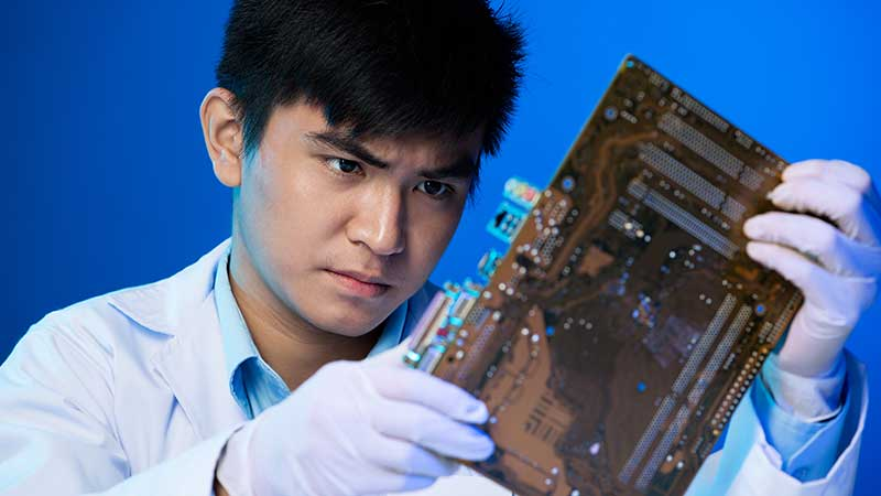 Engineer closely looking at a circuit board with gloves on